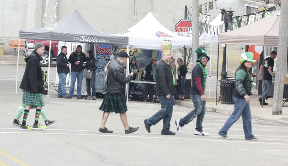 Revelers cross State and Third streets in downtown Alton during Saturday's St. Patrick's Day celebration.
