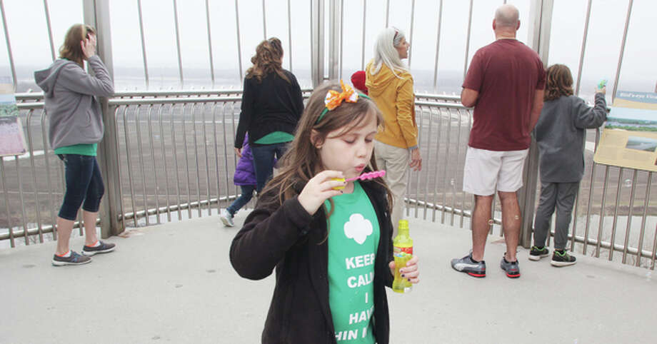 Caroline Robien, 8, a member of Girl Scout Troop 802, based in East Alton, blows bubbles on the top observation deck of Lewis and Clark Confluence Tower in Hartford Saturday. The troop spent part of the day volunteering and exploring the site as part of the celebration of the 104th birthday of the Girls Scouts. Photo: Scott Cousins/For The Telegraph