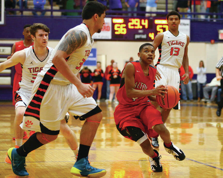 Alton's Ty'ohn Trimble, right, drives the lane against Edwardsville's AJ Epenesa Tuesday night in the semifinals of the Collinsville Class 4A Sectional at Fletcher Gym. Alton won the game 63-59. Credit: Billy Hurst - For the Telegraph Photo: Billy Hurst | For The Telegraph