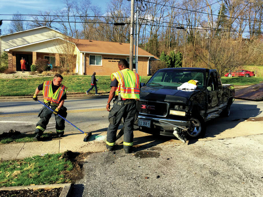 Members of the Alton Fire Department clear glass and debris from the sidewalk after a crash in the 1900 block of Brown Street between Mills Avenue and Rock Springs Drive Monday afternoon. The section of road is notorious for traffic incidents. Photo: Kelsey Landis | The Telegraph