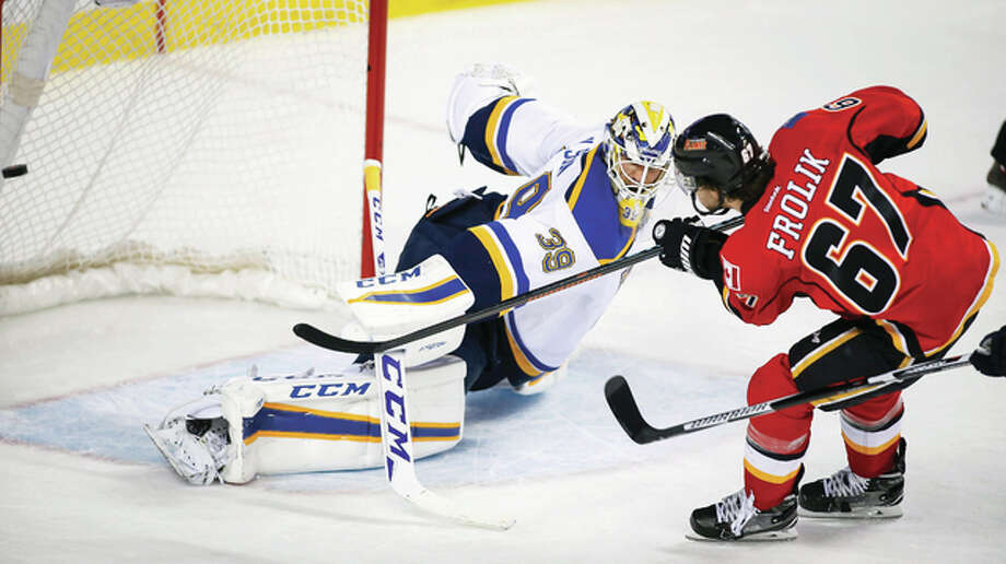 Calgary's Michael Frolik scopres a goal against Blues goalie Anders Nilsson, left, Monday night in Calgary. The Flames won 7-4. Photo: AP Photo