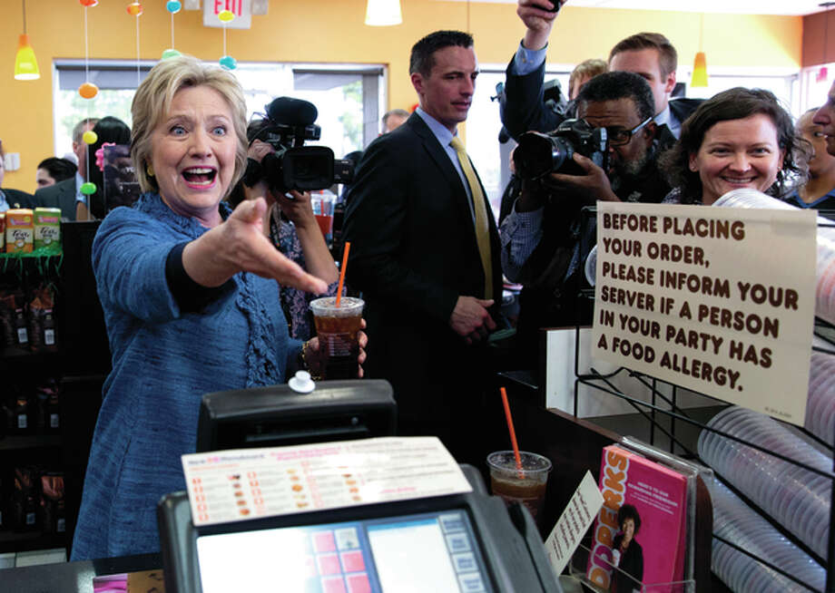 Democratic presidential candidate Hillary Clinton reaches to shake and employees hand behind the counter as she holds her iced tea during a visit to Dunkin' Donuts in West Palm Beach, Fla., Tuesday, March 15, 2016. Clinton faces Democratic rival Bernie Sanders in primary contests in five states on Tuesday: North Carolina, Florida, Ohio, Missouri and Illinois.