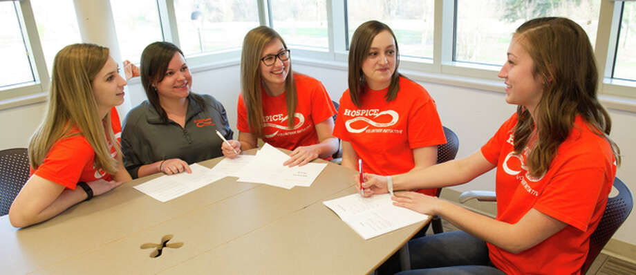 Hospice Volunteer Initiative members, from left, Erika Kuenstler, Jessie Johnson, Katelyn Fryman, Ashleigh Lupton and Maddie VanDaele collaborate on the design and layout of the memory books.