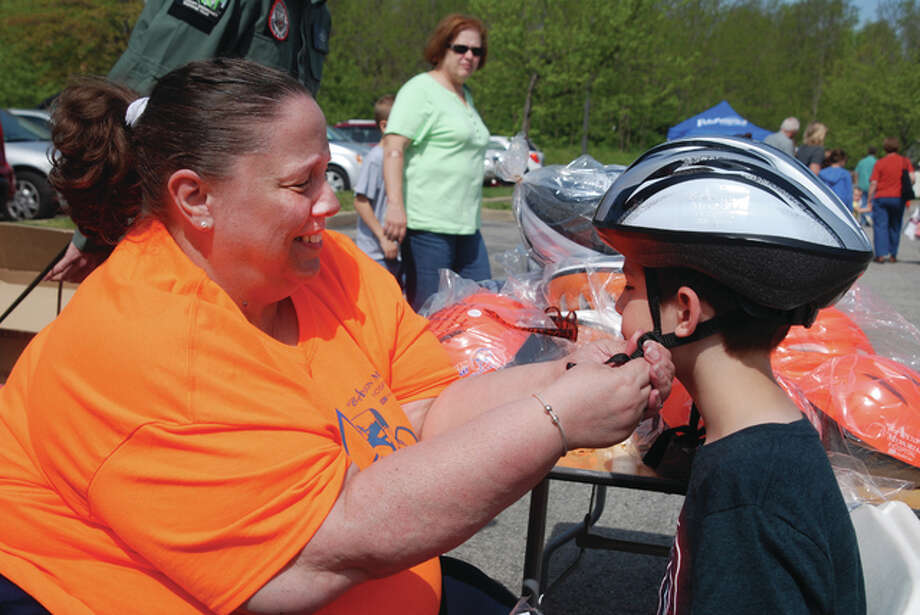 Registered nurse Debbie Woelfel, pictured, will serve as a member of the Illinois Poison Advisory Board. Shown here, Woelfel fits a child with a bike helmet at Alton Memorial Hospital's Family Safety Fest. Photo: For The Telegraph