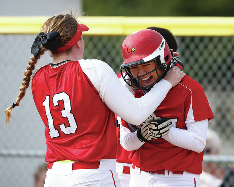 Alton's Tami Wong (right) is congratulated by teammate Brittany Roady after Wong's home run in the Redbirds' 11-0 nonconference victory over the East Alton-Wood River Oilers on Tuesday in Wood River. Photo: Billy Hurst / For The Telegraph