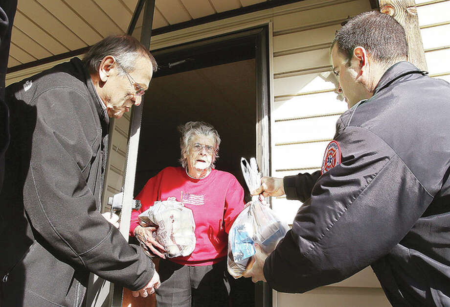 Godfrey Mayor Michael McCormick, left, and Godfrey Fire Chief Erik Kambarian, right, deliver the Meals on Wheels to Godfrey resident Evelyn Allen, 85, Tuesday on Shannon Drive. Alton Mayor Brant Walker was also lending a hand with deliveries Tuesday.