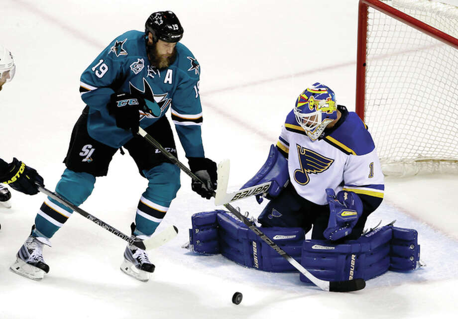 Blues goalie Brian Elliott (1) stops a shot next to San Jose Sharks' Joe Thornton (19) during the third period Tuesday night in San Jose. Photo: AP