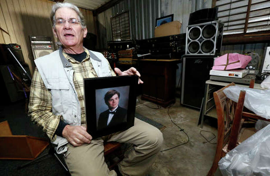 In this March 20, 2016 photograph, Michael Usry Sr. holds a portrait of his then 19-year-old son, Michael Jr., at his Clinton, Miss., garage. Usry recalls how his son became a prime suspect for a short time in a Idaho Falls murder and rape case, although never charged, because of DNA Usry donated to a genealogical research effort backed by the Mormon Church and operated by Brigham Young University scientists as part of the church's deep involvement in genetic research.