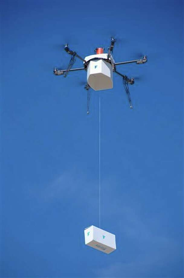 In this Friday, March 25, 2016, photo provided by Flirtey, an independent drone delivery company, shows the first fully autonomous, FAA-approved urban drone delivery, a box with bottled water, emergency food and a first aid kit in a residential setting without the help of a human to manually steer it in Hawthorne, Nev. Flirtey CEO Matt Sweeney announced Friday the six-rotor drone flew itself about one-half mile and lowered the package outside a vacant residence in Hawthorne, about 140 miles southeast of Reno.