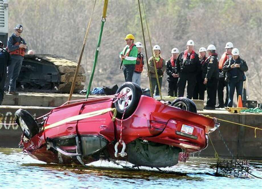 Representatives for several agencies watch from a barge as a vehicle is lifted from the water on Saturday, March 26, 2016 in Fort Thomas, Ky. Crews recovered a body from the car, that went over a barrier after a 12-vehicle crash on the Combs-Hehl Interstate 275 bridge on March 15.