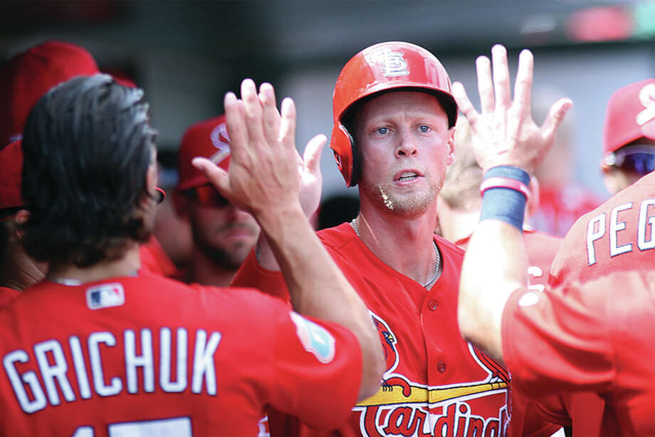 Cardinals outfielder Jeremy Hazelbaker is congratulated by Randal Grichuk and the rest of his teammates Wednesday after scoring a run against the Miami Marlins at Roger Dean Stadium in Jupiter, Florida. Photo: Nathan Woodside | The Telegraph
