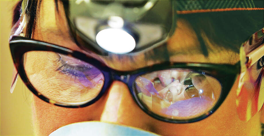 Miles of Smiles dental hygienist Nikki Carls works Tuesday on the teeth of Lewis and Clark Middle School student Blake Bailey, 11, as seen reflected in her glasses, right, at the Wood River school Tuesday. The Peoria-based Miles of Smiles organization came and screened children's teeth, cleaning them and sealing them when possible.
