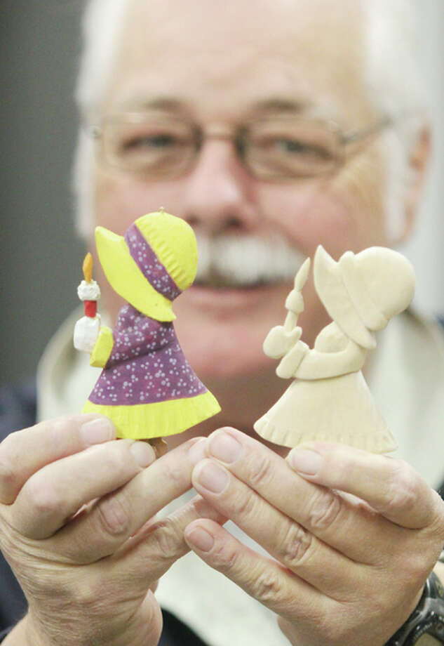 Randy Rhodes, a member of the Woodworking Club at Senior Services Plus in Alton, shows examples of painted and unpainted Christmas ornaments the club made as a fundraiser for the center's Meals on Wheels program.