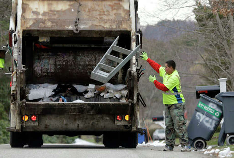 In this Wednesday, March 23, 2016, photo, a sanitation worker throws a stepladder into his truck in North Andover, Mass. On Friday, April 1, 2016, the government issues the U.S. jobs report for March. Photo: AP Photo/Elise Amendola