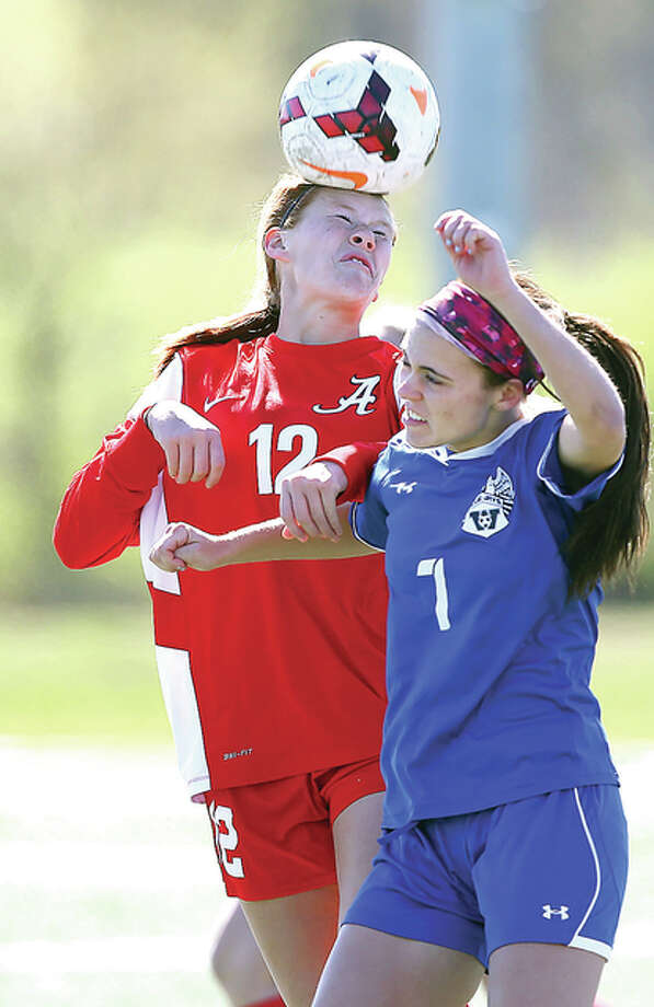 Alton's Lexi Schrimpf, left, heads the ball against Washington's Cassidy Nurnberger Saturday. Photo: Billy Hurst | For The Telegraph