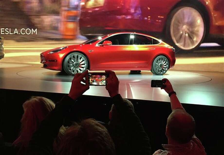 Tesla Motors unveils the new lower-priced Model 3 sedan at the Tesla Motors design studio in Hawthorne, Calif., Thursday. It doesn't go on sale until late 2017, but in the first 24 hours that order banks were open, Tesla said it had more than 115,000 reservations. Long lines at Tesla stores, reminiscent of the crowds at Apple stores for early models of the iPhone, were reported from Hong Kong to Austin, Texas, to Washington, D.C. Buyers put down a $1,000 deposit to reserve the car.