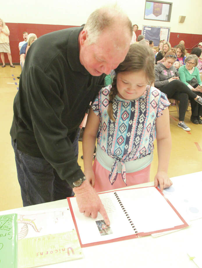 "Don Elledge and his granddaughter, Kylen Johnson, a fourth-grader at Lewis and Clark Elementary School in Wood River, look over her book, ""The Best Teachers Ever,"" at a Young Authors award program Thursday night."