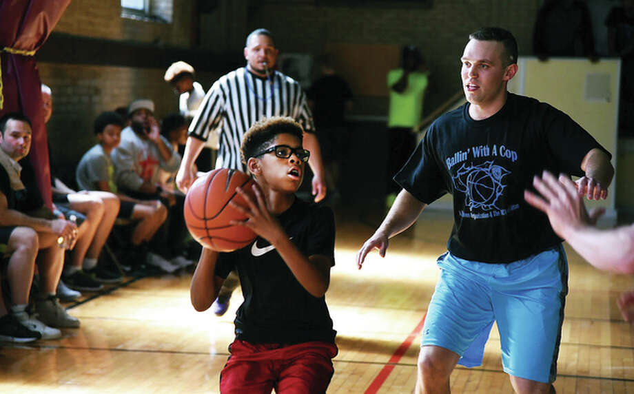 Area police officers and youth came together for Alton's first Ballin' With A Cop event, hosted by the YWCA.The event was organized with Romell Jones, an Alton boy killed in a drive-by shooting while waiting on a ride to basketball practice last year.