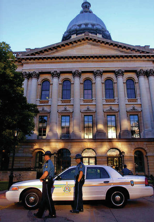 In this Sept. 21, 2004, file photo, Illinois Secretary of State Police secure the entrance of the Illinois State Capitol building after an unarmed security guard was shot and killed in Springfield, Illinois. The Illinois budget foul-up took on safety implications last winter when Secretary of State Police had to make cash pickups at driver's licenses facilities after an unpaid armored-truck company temporarily quit. Illinois Secretary of State Jesse White's office told The Associated Press that pairs of armed police officers made the pickups during off-hours for 15 weeks. Photo: (AP Photo/Seth Perlman, File)