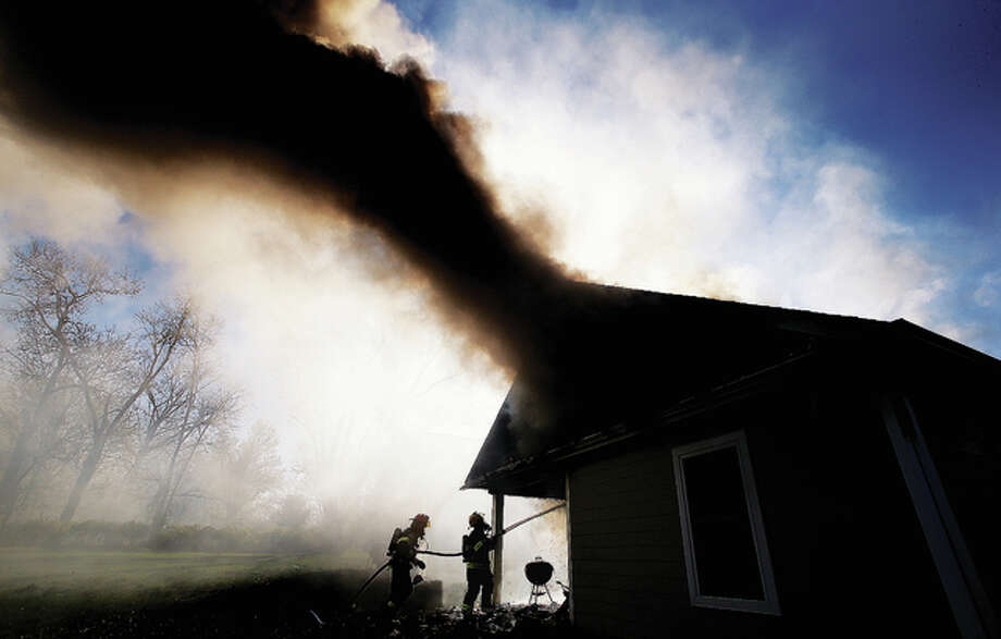 Alton firefighters direct a hose on flames and smoke billowing from the attic of 913 Gold St. in Alton Monday afternoon after wind swept a fire in the kitchen into the attic, gutting the home. A pot was apparently left on a kitchen stove starting the fire. Alton called for assistance from East Alton firefighters at the scene. Fire officials said a door was left open on the house allowing the strong winds to blow through the structure like a wind tunnel. The heavy, black smoke was visible for many blocks. Photo: John Badman | The Telegraph
