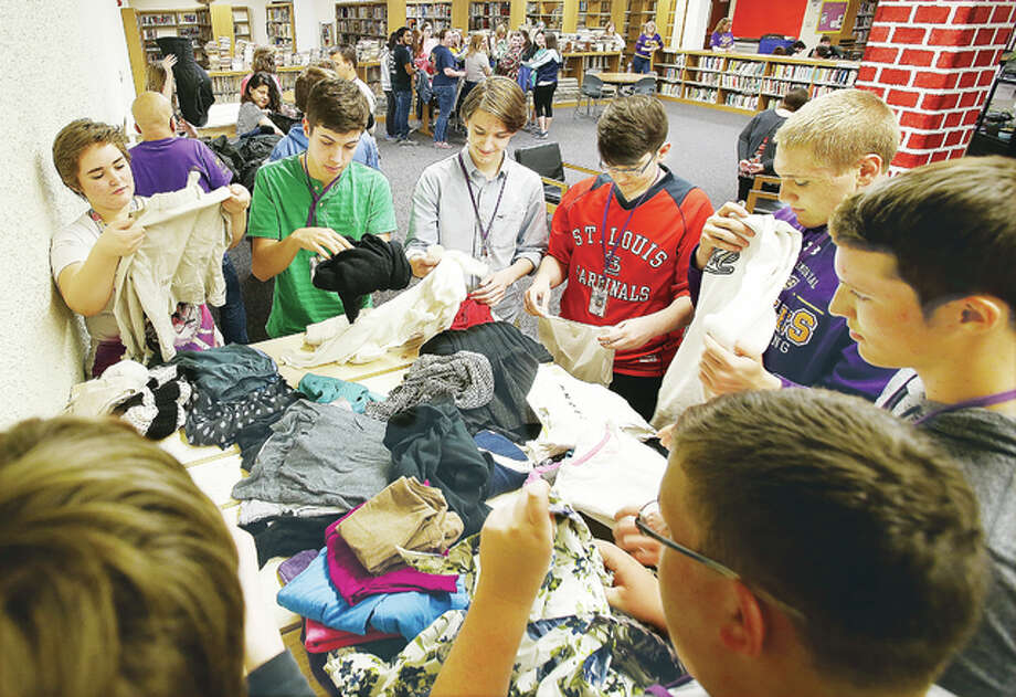 Civic Memorial High School National Honor Society students, in Bethalto, fold clothes collected during a fundraising drive for a cafe project planned for construction as part of the school's Secondary Transition Experience Program (STEP). Teachers with STEP are planning a cafe that will STEP students develop work skills while offering all students a place to relax. The cafe program is modeled after a similar program at Roxana High School. More fundraisers are planned to meet the $3,000 need to finish and equip the cafe. Photo: John Badman | The Telegraph