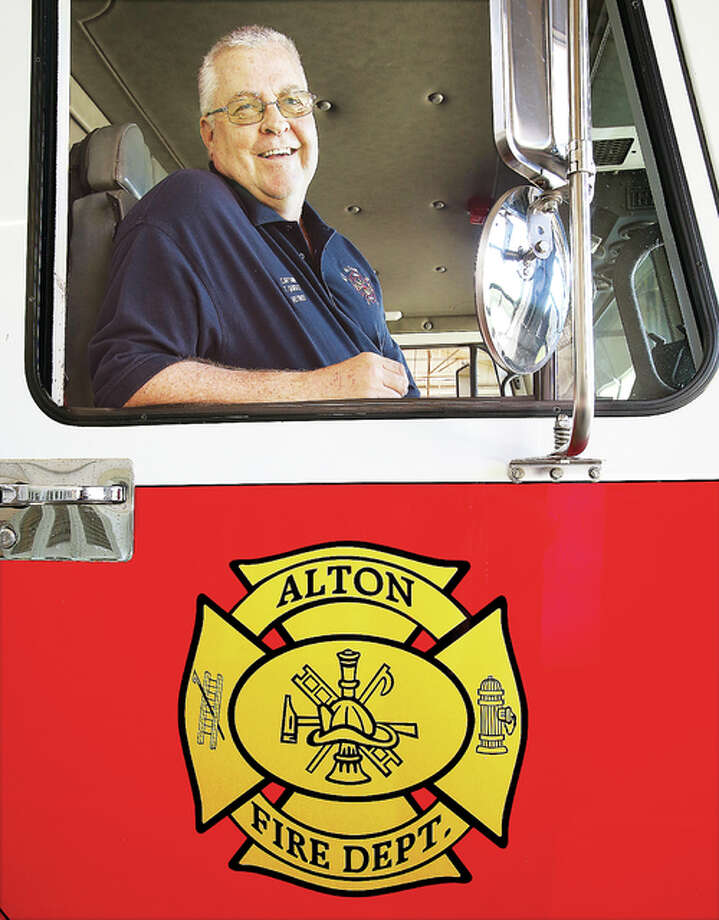Alton Fire Department Capt. Tim Quigley, 55, sitting in the captain's seat of a pumper truck, has hung up his helmet after 24 years on the job. Photo: John Badman | The Telegraph