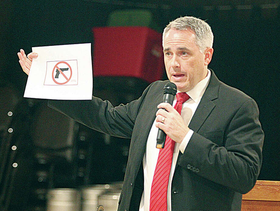 "Madison County State's Attorney Tom Gibbons holds a copy of the ""magic sign"" that must be displayed to prohibit people with concealed carry permits from taking firearms into a building. He noted that the law requires the sign to be an exact shape and size. Gibbons was talking about the state's concealed carry license law at a meeting of the Alton-Godfrey Rotary Monday evening."