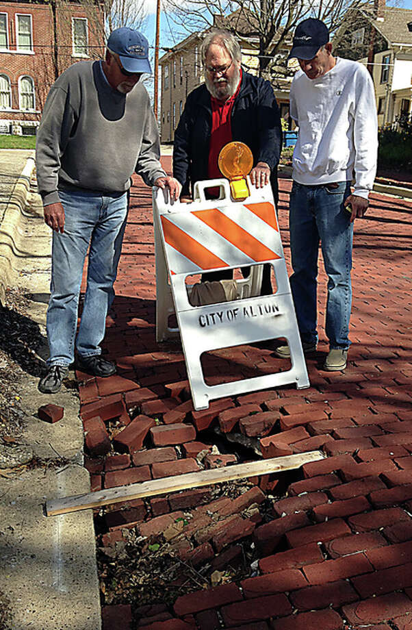 Christian Hill homeowners, from left, Charlie Stocker, Tom Wilkinson and Dale Lewis inspect one of three sinkholes on Mamie Street over which someone placed a board to further warn pedestrians or motorists of the void.
