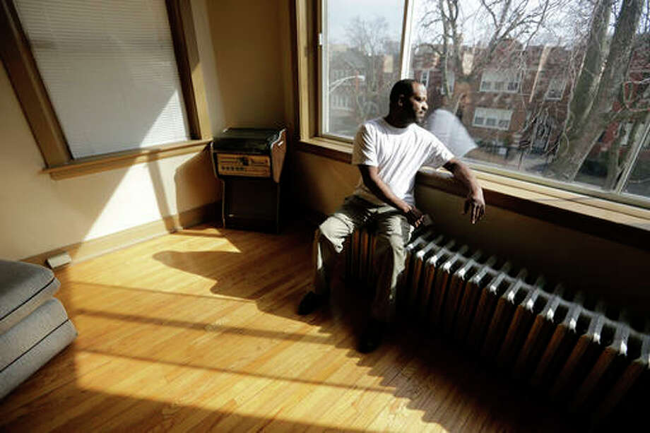 "In this March 8, 2016 photo, Darnell Johnson, 50, a resident of a sober home in Chicago, looks out the window of his apartment. Johnson says he was a ""weekend social drinker, but it would last all day."" Now when he smells alcohol or sees how it affects others, he remembers the bad times."