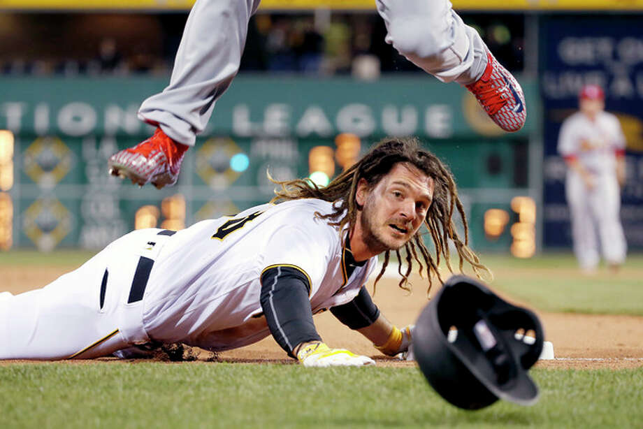 Pittsburgh's John Jaso slides into third with a triple as Cardinals third baseman Matt Carpenter leaps over him to retrieve an overthrown ball in the fifth inning Wednesday in Pittsburgh. Jaso was allowed to score after the overthrown ball went into the stands. Photo: Gene J. Puskar | AP Photo