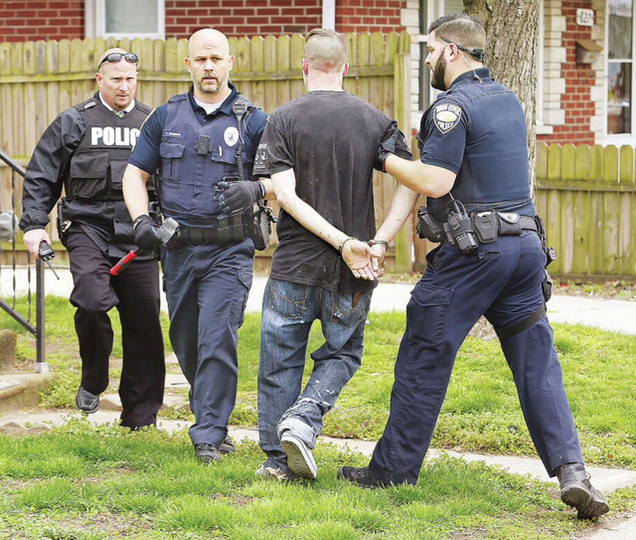 Wood River police remove a man from a house Thursday in the 800 block of State Street after he held police at bay for nearly an hour, apparently refusing to come out of the home. The man was wanted on a felony warrant from Madison County and was a suspect in an earlier incident Thursday in which the windows were smashed out of a vehicle in Wood River. Police surrounded the house and had to call in an off-duty K-9 officer, who apparently went into the house with his partner and apprehended the suspect.