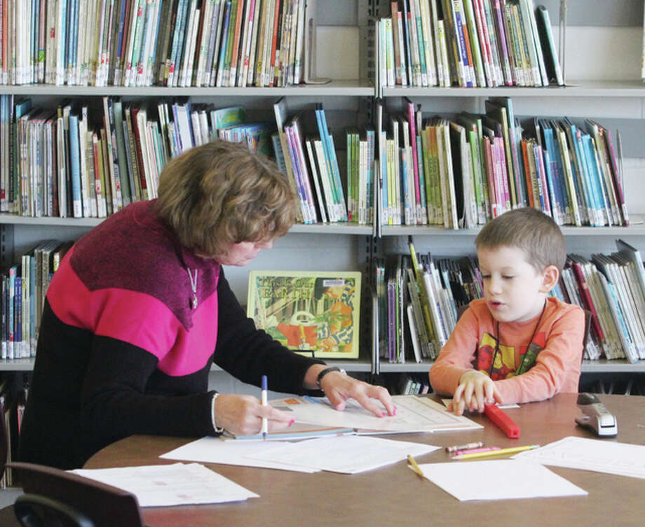 Kindergarten teacher Ruth Miller shows Aaron Maupin what to do during a kindergarten screening at Grafton Elementary School.