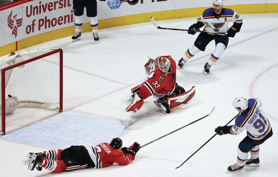 The Blues' Vladimir Tarasenko (right) scores wh8ile Blackhawks goalie Scott Darling (middle) and defenseman Brent Seabrook (left) scramble to stop the shot during overtime Thursday night in Chicago. The Blues won 2-1. Photo: Associated Press