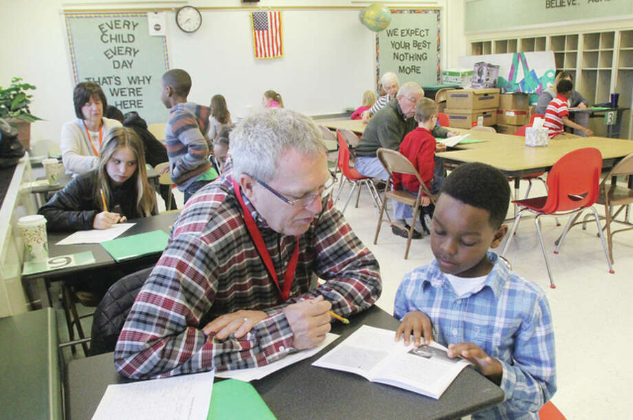 Volunteer Steve Forbes listens as Gilson Brown Elementary School second-grader Darence Edwards reads to him as part of the Reach Out and Read program in the Alton School District. All of the Alton School District's elementary schools participate in the program, which pairs volunteers with children who read books to them.