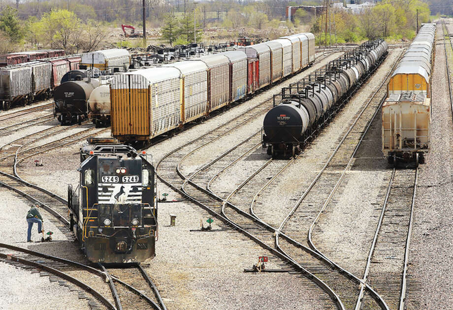 A worker in the Norfolk & Southern freight yard in Alton, left, throws a track switch this week as an engine works on moving freight cars around. Rail is an important component of the St. Louis Regional Freightway's transportation and logistics network that includes highways, airports and the Mississippi River.