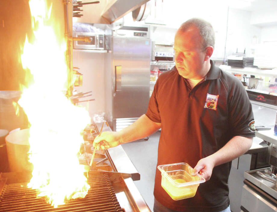 "Scott Cousins/The Telegraph Brad Hagen, executive chef and partner/owner of the Grafton Oyster Bar, cooks an order of char-grilled oysters at the restaurant this week. The restaurant opened March 1 and has ""exceeded expectations"" in the first month, according to Hagen."