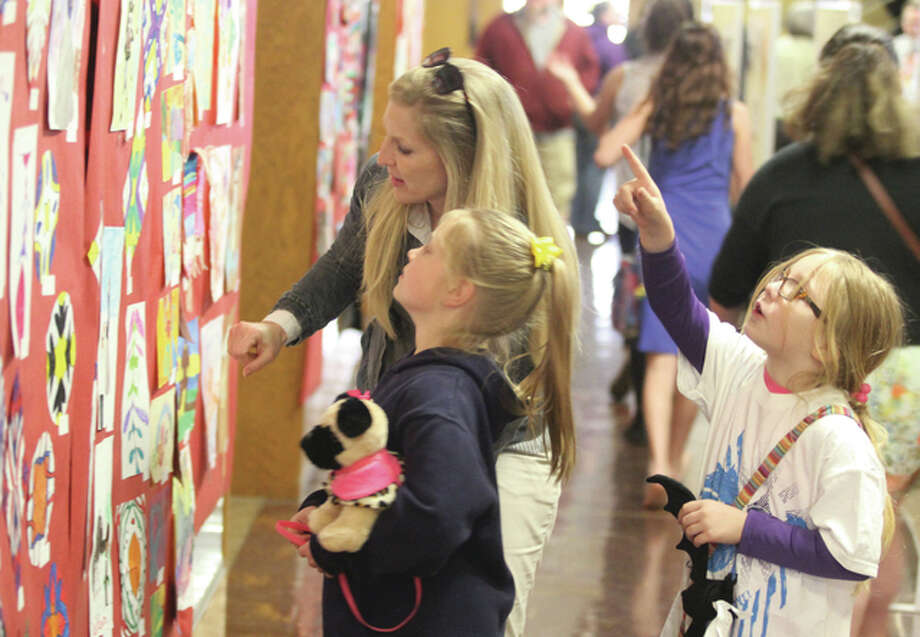 Heather Johnson, principal of Lewis and Clark Junior High School, her daughter, Olivia Johnson (left) and Tabitha McVey look over artwork during the 5th Annual Tri-District Fine Arts Festival, held Thursday in Memorial Gymnasium at East Alton-Wood River High School. The festival featured band and choral performances, as well as hundreds of exhibits by students in the EAWR High School, Wood River-Hartford Elementary and East Alton Elementary school districts.