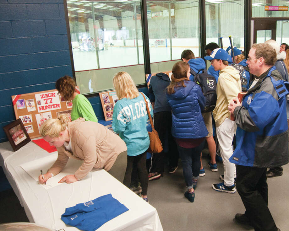 Several people turned out on Sat. morning at the East Alton Ice Rink Arena to pay tribute to Zach Hunter a Junior at Marquette Catholic High School and sign some posters to be delivered to him and hung up in his hospital room at Barnes-Jewish Hospital in St. Louis where he is being treated after a car accident on Friday April 1st.