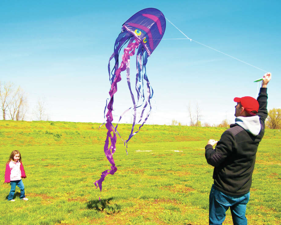 Matt Rutherford, of Edwardsville, makes an effort to get his kite up in the air while his daughter, Anna, looks on Saturday at the Lewis and Clark Confluence Tower Wind Festival. Photo: Dan Cruz | For The Telegraph
