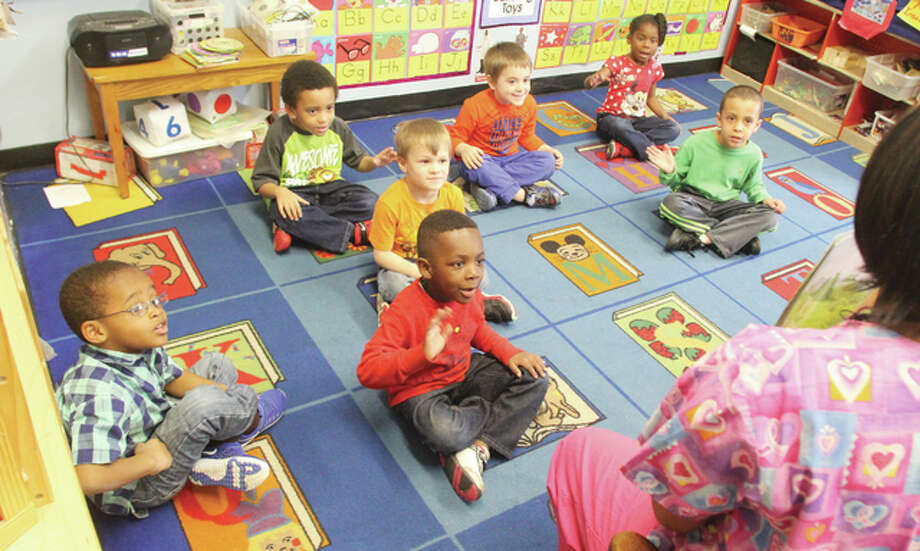 "Students in teacher Lori Terrell's pre-K class at the Kreative Kids Learning Center in Alton do motions to go along with a story she is reading late Monday morning. The center was among childcare providers nationwide celebrating ""The Week of the Young Child."""