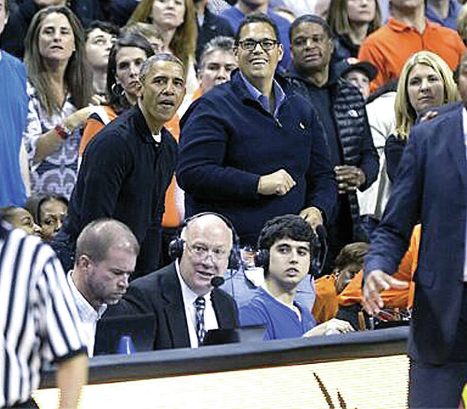 Scott Lynn, front wearing headset, broadcasts a 2013 basketball game as basketball fan President Barack Obama watches the game behind him. Photo: Submitted Photo