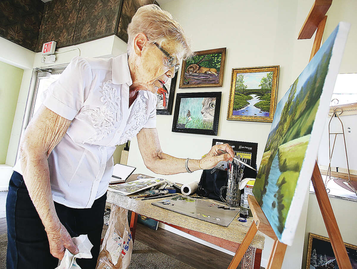 Artist Rita Cooper, of O'Fallon, Illinois, worked on painting a landscape during the soft opening where people could watch and talk to her about her work, some of which currently is on display.