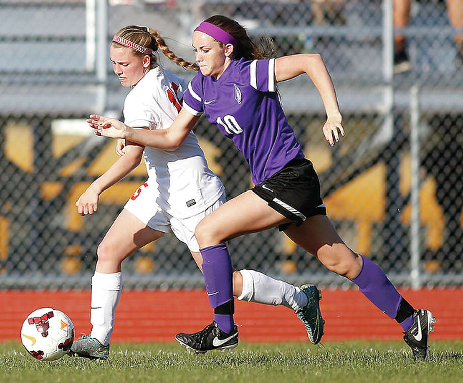 Collinsville's Chayse Richardson (10) and Alton's Katie Kercher (15) chase the soccer ball during Southwestern Conference action Thursday at the Alton High soccer field. Richardson had an assist for the Kahoks in their 4-0 victory. Photo: Scott Kane | For The Telegraph