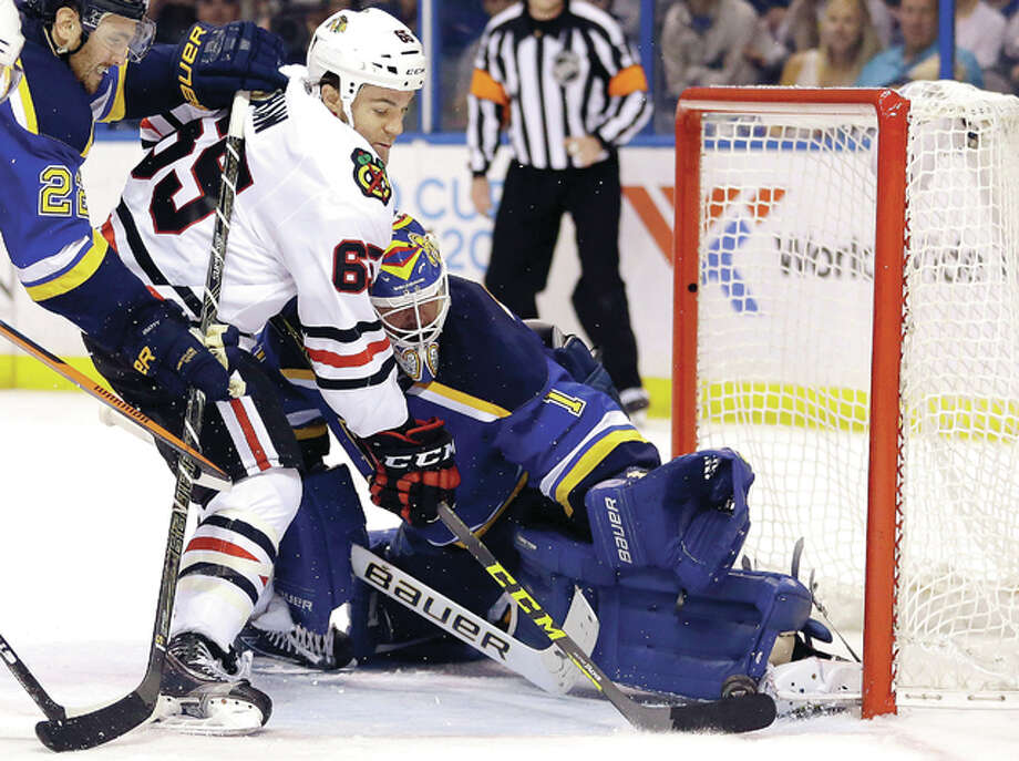 Chicago Blackhawks' Andrew Shaw, left, scores past St. Louis Blues goalie Brian Elliott during the third period in Game 2 of an NHL hockey first-round Stanley Cup playoff series Friday, April 15, 2016, in St. Louis. The Blackhawks won 3-2. (AP Photo/Jeff Roberson) Photo: Jeff Roberson | AP Photo