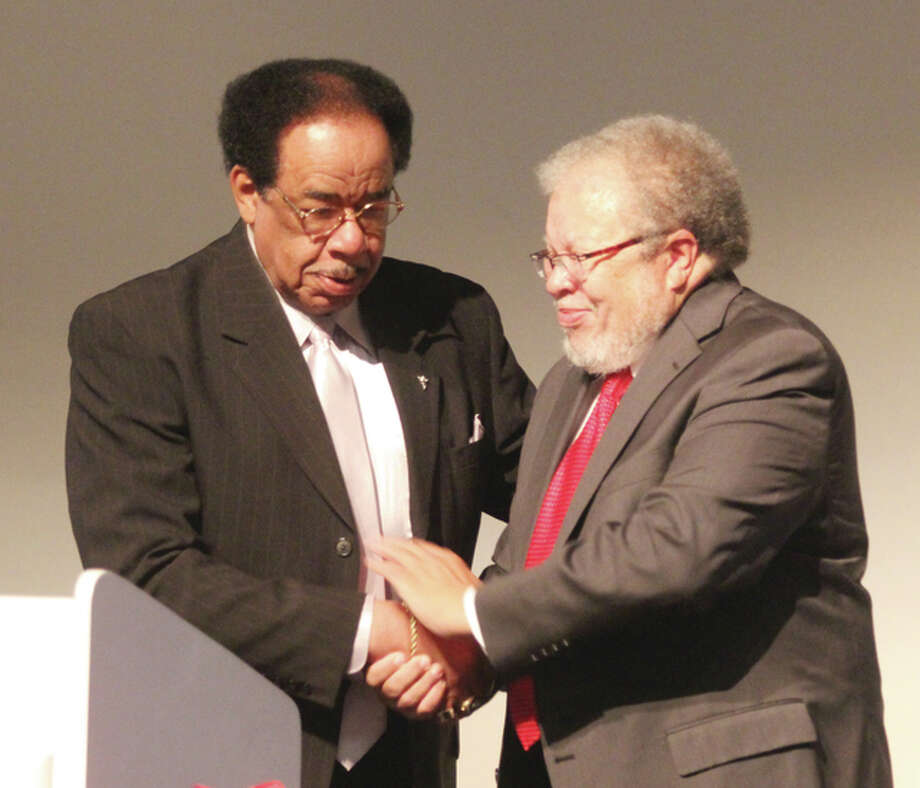 Bobby Collins Sr., left, winner of a community service award, is congratulated by retired Judge Duane Bailey, chairman of the Madison County Urban League board of directors, at the organization's 39th annual dinner, held Thursday at Lewis and Clark Community College.