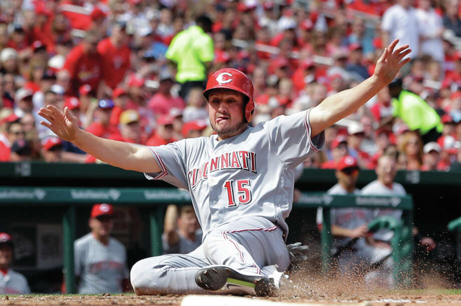 The Reds' Jordan Pacheco slides safely across the plate during the sixth inning of Cincinnati's win over the Cardinals on Saturday at Busch Stadium. Photo: Associated Press