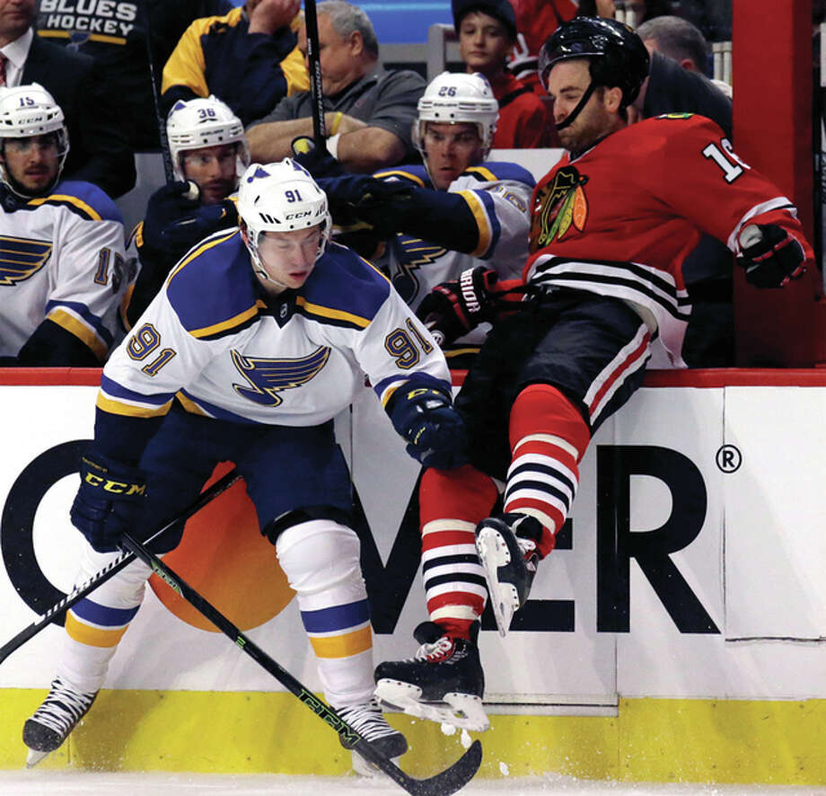 The Blackhawks' Andrew Ladd (right) is checked by the Blues' Vladimir Tarasenko during the first period in Game 3 of a first-round Stanley Cup playoff series Sunday in Chicago. Photo: Associated Press
