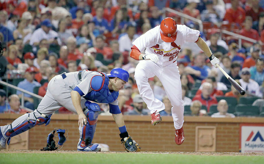 Chicago Cubs catcher Miguel Montero, left, reaches for a dropped third strike as Cardinals right fielder Stephen Piscotty leaps out of the way before being thrown out at first during the seventh inning of a Monday in St. Louis. Photo: AP