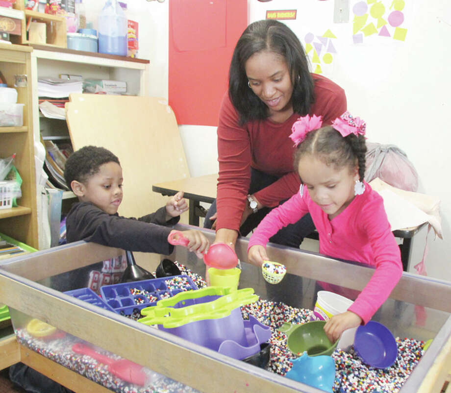 Jameisha McCarter and her children, Kalib and Alliyah Anderson, both 4, look over one of the learning centers in Maxine's Day Care Center in Alton. Maxine's is the only child care center in the Riverbend offering after-hours child care. Without adequate child care, McCarter, who works evenings at Challenge Unlimited, said she would not be able to keep her job. Photo: Scott Cousins/The Telegraph