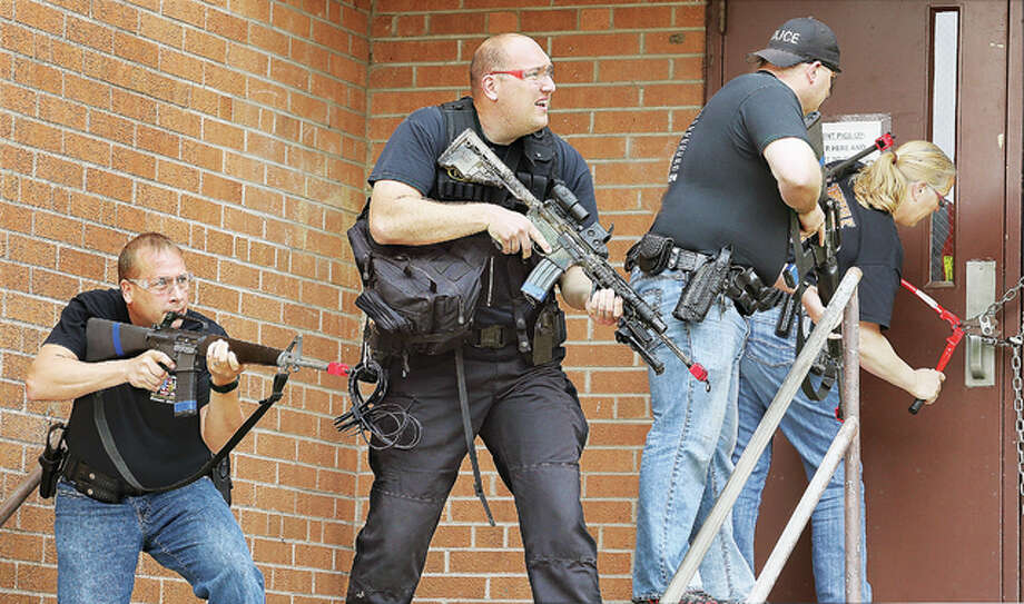 """Alton police officers assume a defensive position Tuesday, left, behind Horace Mann School in Alton as other officers use bolt cutters to remove a chain on a door during an """"active shooter"""" drill involving police and firefighters working together. Instead of waiting for a tactical team, consensus in law the enforcement community is for first responding officers to enter the building as quickly as possible to eliminate the threat, which minimizes casualties."""